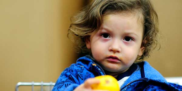 Child with apple supported by Foodbank